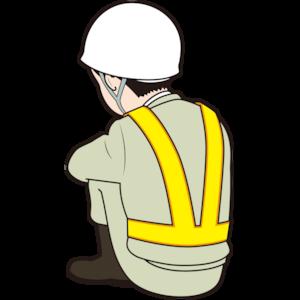 膝を抱える男性作業員