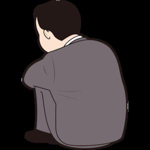膝を抱える太った男性会社員