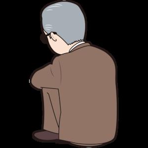 膝を抱えるシニア男性会社員